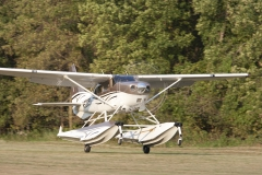 Cessna 206 on Amphibious Wipline 3450 Floats Leaving the Grass