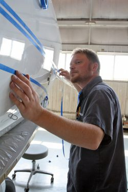 A Wipaire paint technician carefully applying masking tape following the striping design.